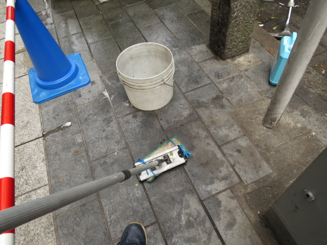 飲食店のゴミ集積場の御影石バーナー仕上げに油の濃い濡れジミがのサムネイル
